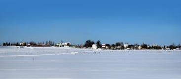 与一个村庄的农村风景在雪原以后的地平线的在明亮的晴天全景的清楚的蓝色无云的天空下 库存照片