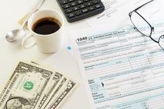 与一个杯子的收入税单形式无奶咖啡、金钱和玻璃在桌上 免版税库存图片
