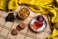 与一个杯子的燕麦粥饼干在老木背景的土耳其茶,一杯茶用葡萄干,一杯茶用巧克力 图库摄影