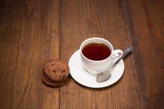 与一个杯子的Stilllife在木桌上的红茶 免版税库存图片