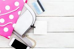 与一个标签的女性袋子在一张桃红色包裹、电话和信用卡 库存照片