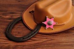 与一个棕色牛仔帽和马鞋子的一枚警长徽章 免版税库存照片