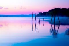 与一个湖和山在背景中和树的美好的风景在水中 蓝色和紫色颜色口气 库存照片