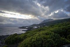 与一个火山的熔岩海岸线在日落的剧烈的天空下在Pico海岛上  库存照片