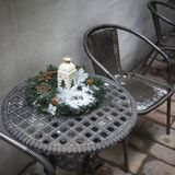 与一个灯笼和一个云杉的花圈的圣诞节构成用在用雪盖的铁桌上的红色山楂树莓果 免版税库存图片