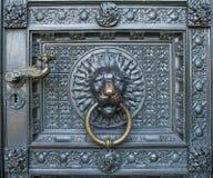 与一个狮子头的一个古铜色敲门人在科隆大教堂的门 免版税库存图片