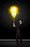 与一个环境友好的电灯泡的商人 免版税库存图片