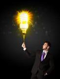 与一个环境友好的电灯泡的商人 免版税图库摄影