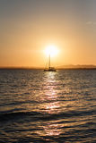 与一个现出轮廓的小船航行的日落 库存照片