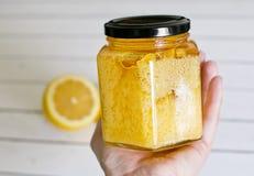 与一个瓶子的柠檬在轻的背景的蜂蜜 免版税库存图片