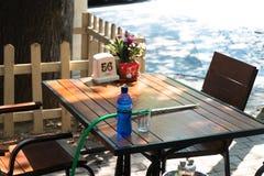与一个瓶的咖啡馆桌水和玻璃和椅子 免版税图库摄影