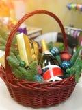 与一个瓶的圣诞节篮子香槟云杉礼物甜点和分支  免版税库存图片