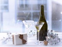 与一个瓶的静物画香槟、两块玻璃和礼物盒 免版税库存图片