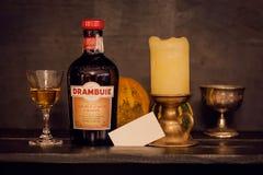 与一个瓶苏格兰威士忌利口酒,一个蜡烛的侍酒者静物画和倒空名片 免版税库存照片
