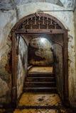 与一个生锈的被雕刻的格子的门在一间老地下室 库存照片