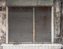 与一个生锈的路辗快门门的老大厦 免版税库存图片
