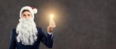 与一个电灯泡的商人圣诞老人在他的手上 免版税库存照片