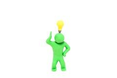 与一个电电灯泡的小彩色塑泥木偶在头 免版税库存图片
