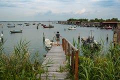 与一个男孩的海风景一个木码头观看的渔船和钓鱼棚子的 免版税库存图片