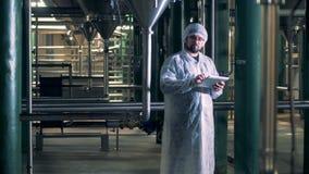 与一个男性工作者身分的啤酒厂设施在它和操作计算机 影视素材