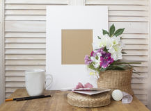 与一个白色框架、杯子和一朵好的花的静物画 免版税库存照片
