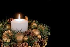 与一个白色蜡烛的圣诞节装饰和在黑背景的杉木苹果 免版税图库摄影