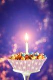 与一个的装饰的生日杯形蛋糕点燃了蜡烛和五颜六色的糖果在黄色背景 假日贺卡 免版税图库摄影