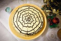 与一个礼物盒的Esterhazy蛋糕在圆的板材 免版税库存照片