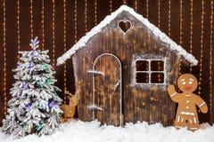 与一个积雪的小屋、姜饼人和圣诞树的圣诞节场面 童话森林装饰 免版税库存照片
