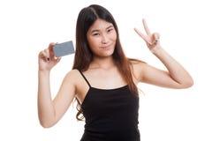 与一个空插件的年轻亚洲妇女展示胜利 库存图片