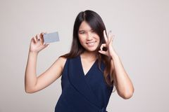 与一个空插件的年轻亚洲妇女展示OK 免版税图库摄影