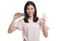 与一个空插件的年轻亚洲女商人展示OK 图库摄影