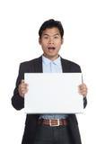 与一个空白的标志的亚洲商人惊奇 库存图片