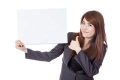 与一个空白的标志的亚洲女实业家翘拇指 免版税库存照片