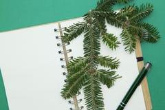 与一个空白的笔记本和一个云杉的分支的绿色圣诞节或新年背景 免版税库存图片