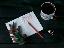 与一个笔记本的静物画有红色题字的2018年,一杯咖啡 免版税库存照片