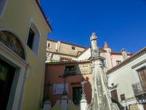 与一个箭头的雕象在房子和天空蔚蓝背景的加泰罗尼亚的中心旁边在马拉泰亚,意大利 免版税库存照片