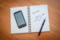 与一个箭头的拉长的心脏在笔记薄 库存照片