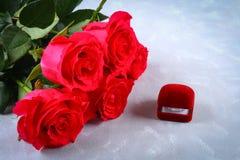 与一个箱子的桃红色玫瑰有在桌上的一个圆环的 概念提案,婚礼,情人节 库存图片