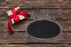 与一个红色圣诞节礼物的老罐子框架在老木backgro 免版税库存图片