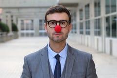 与一个红色小丑鼻子的商人 库存照片