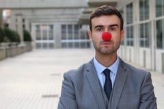 与一个红色小丑鼻子的商人 免版税图库摄影