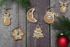 与一个红色球的冷杉分支在木墙壁附近用圣诞节曲奇饼 库存图片