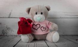 与一个红色礼物袋子的逗人喜爱的小的玩具熊在他的膝部 库存照片