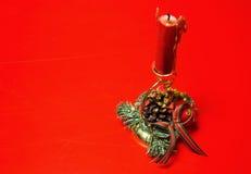 与一个红色蜡烛的圣诞节装饰在被隔绝的红色 库存照片