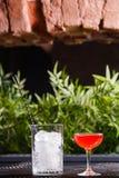 与一个红色酒精鸡尾酒的一块小低玻璃充分在桌上在一个玻璃花瓶清楚的冰大方形的片断旁边  库存图片