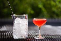与一个红色酒精鸡尾酒的一块小低玻璃充分在桌上在一个玻璃花瓶清楚的冰大方形的片断旁边  免版税库存照片