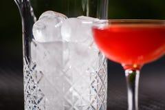 与一个红色酒精鸡尾酒的一块小低玻璃充分在桌上在一个玻璃花瓶清楚的冰大方形的片断旁边  免版税库存图片