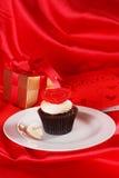 与一个红色重点的杯形蛋糕在配件箱的顶层和礼品在红色缎 免版税库存图片