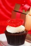 与一个红色重点的杯形蛋糕在配件箱的顶层和礼品在红色缎 图库摄影